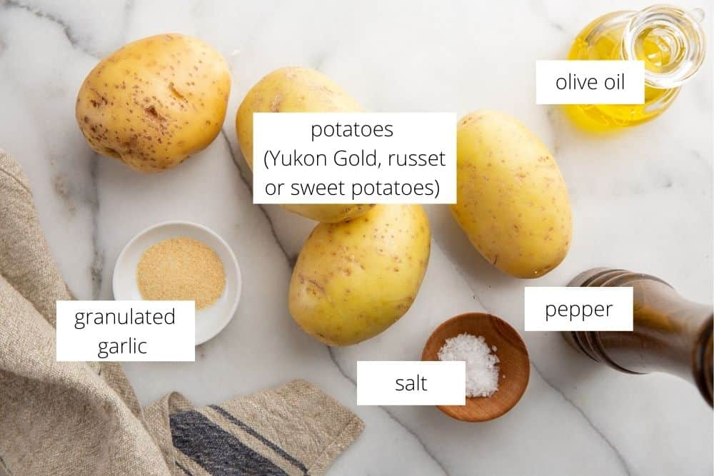 The ingredients for the grilled potatoes recipe on a marble surface with labels.