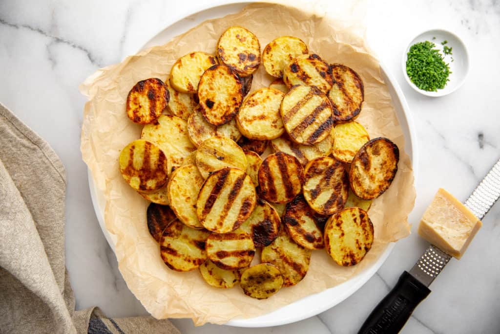 Grilled potatoes on a platter with a block of parmesan cheese and chopped chives alongside.