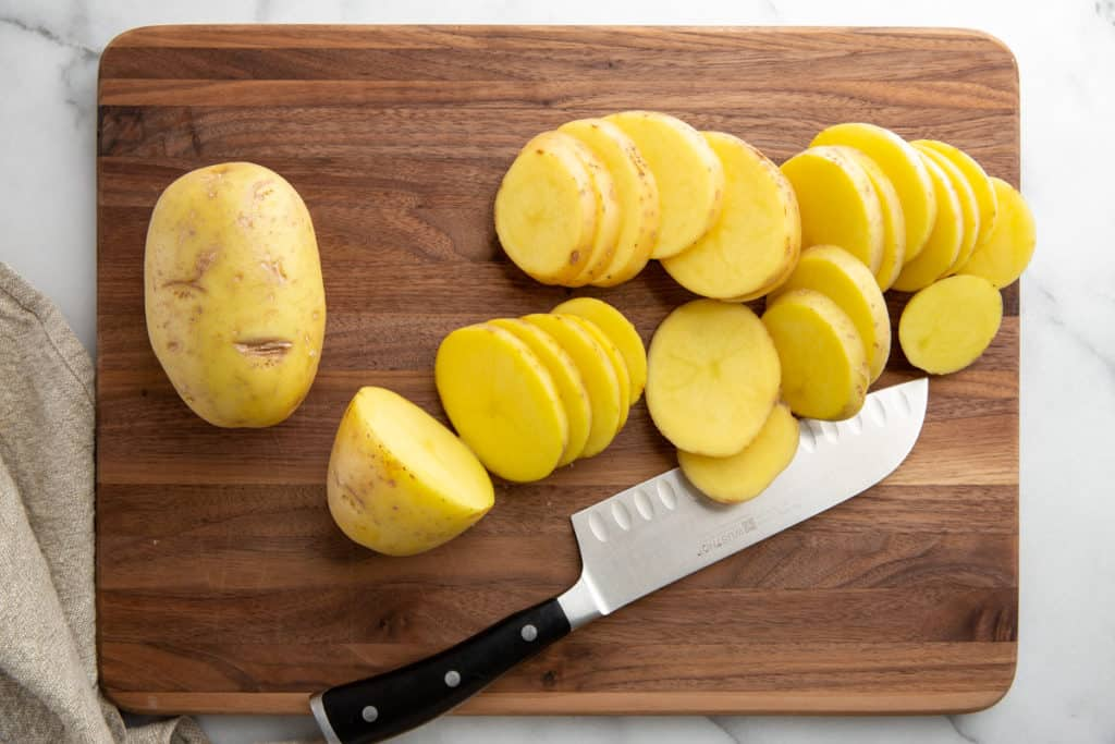 Process shot showing how to slice potatoes for the grill.