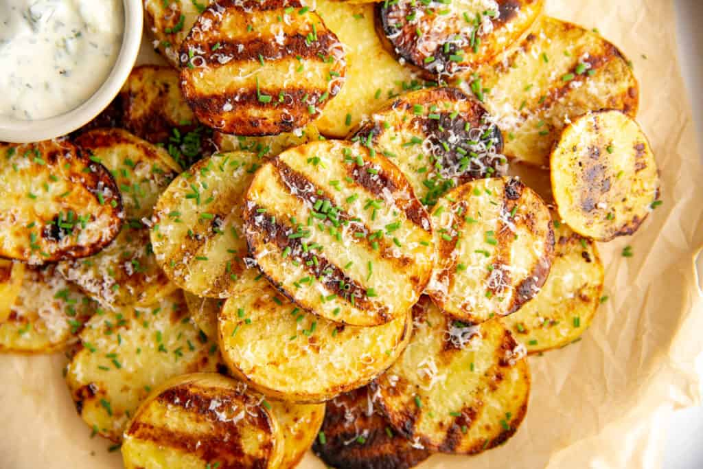 BBQ potatoes on a platter with chives and parmesan cheese.