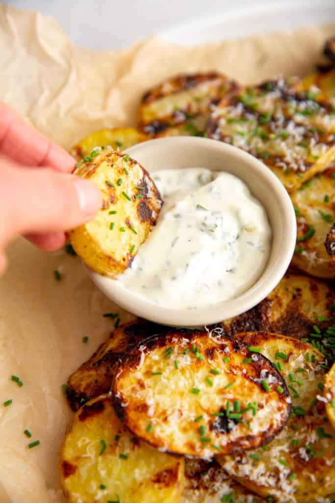 A hand dipping a bbq potato into a bowl of herbed aioli.