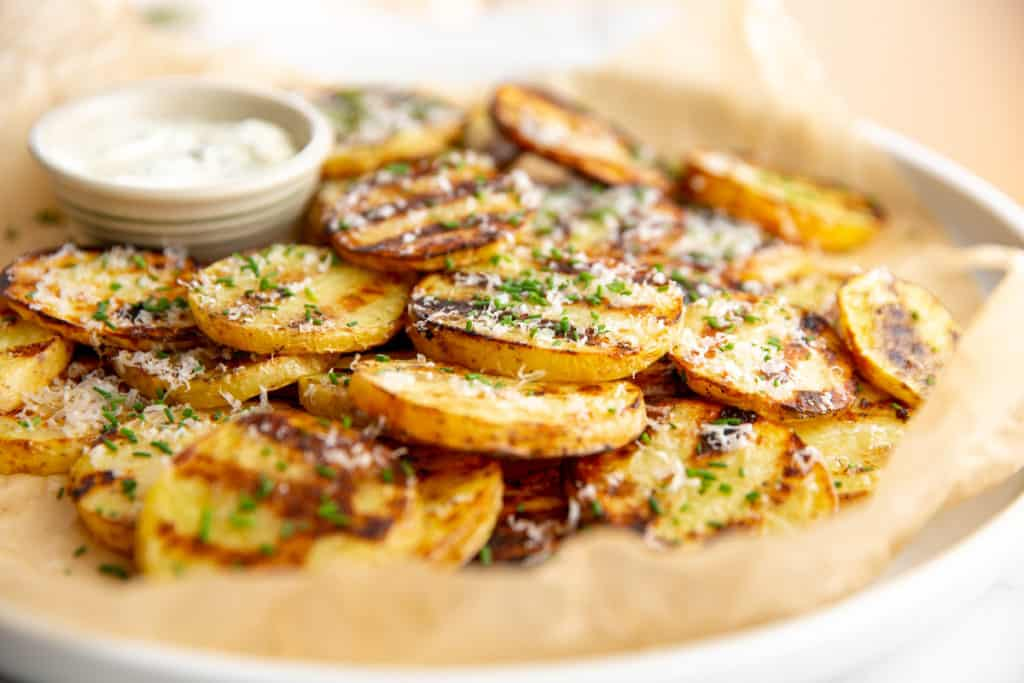 Grilled potatoes on a platter topped with chives and parmesan cheese.