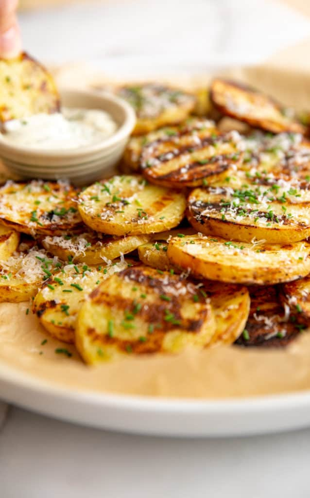 Grilled potatoes on a platter with a small bowl of herbed aioli in the background.