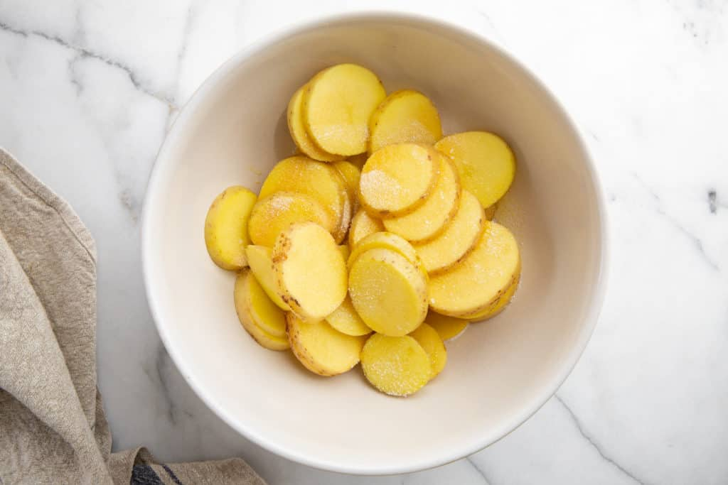 Process shot showing sliced potatoes and olive oil in a bowl for the grilled potatoes recipe.