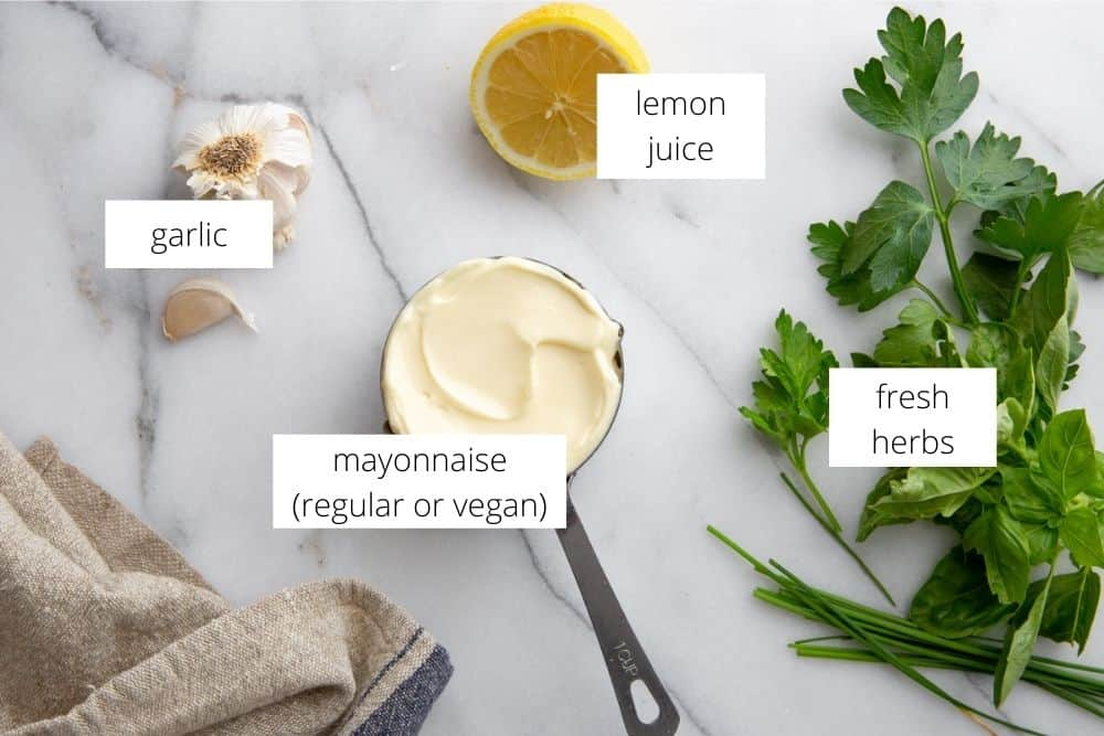 All of the ingredients for the herbed aioli on a marble surface with labels.