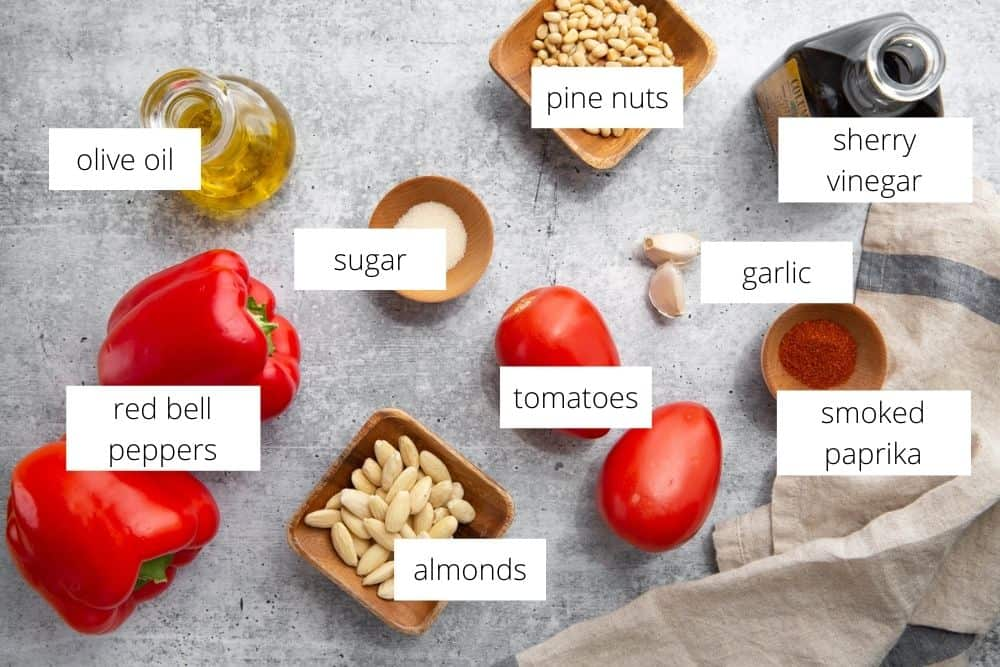 All of the ingredients for the romesco sauce recipe arranged on a work surface with labels.