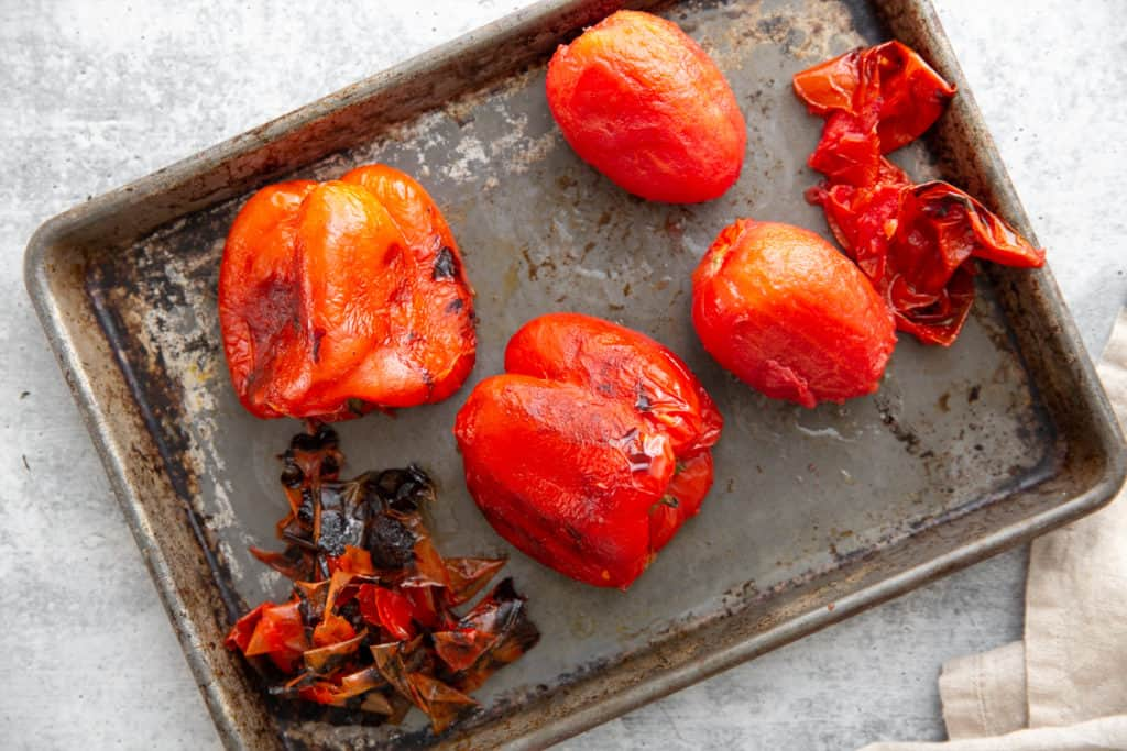 Process shot showing grilled whole bell peppers and plum tomatoes on a sheet pan with their skins removed.