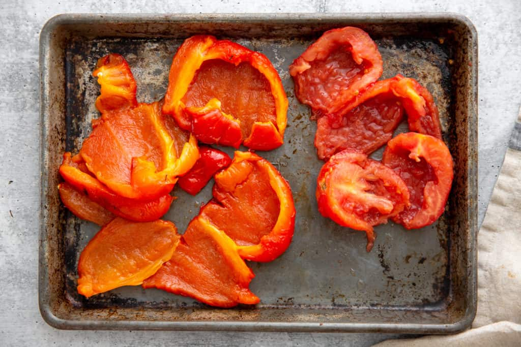 Roasted red peppers and tomatoes on a sheet pan.