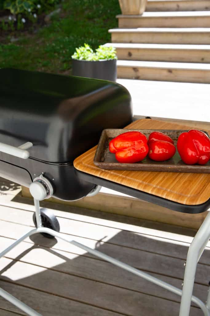 A pan of peppers and tomatoes on the wooden cutting board of a Spark Grill.