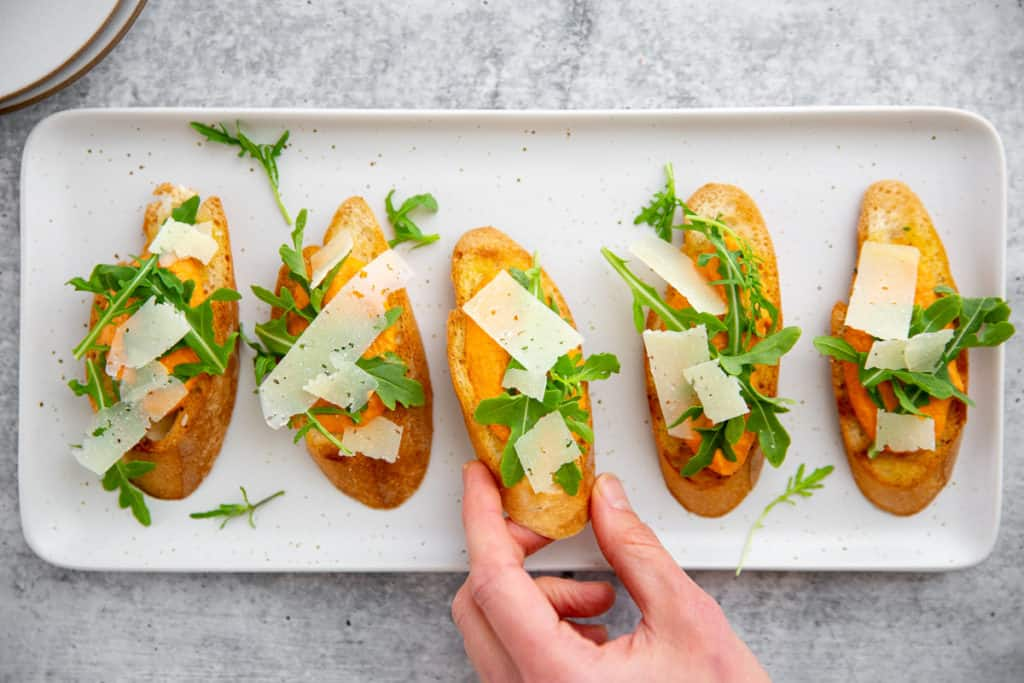 A hand grabbing a romesco crostini off a platter.