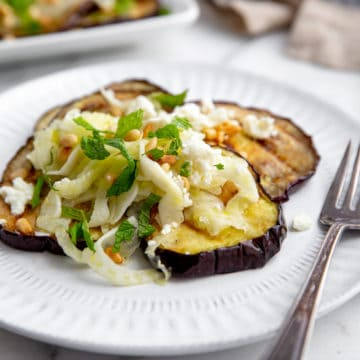 Grilled eggplant salad on a plate with a fork.