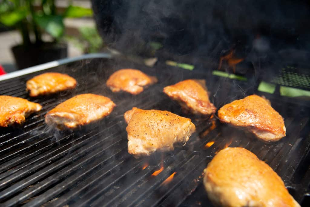 Chicken thighs cooking on a Spark Grill.