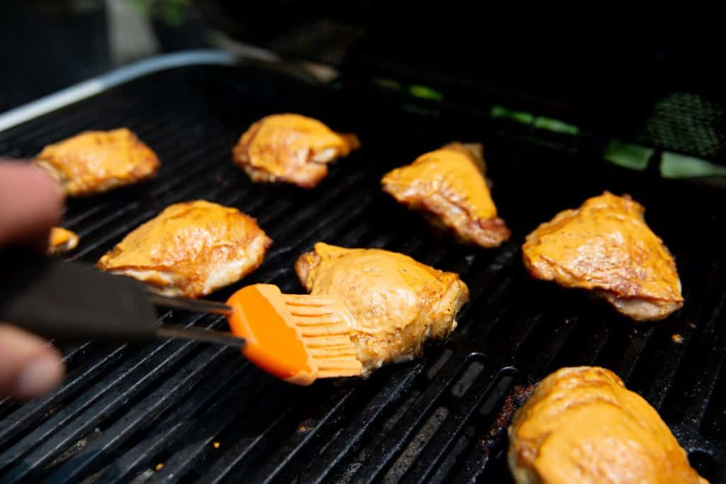 Process shot showing how to brush chicken thighs with romesco sauce while grilling.