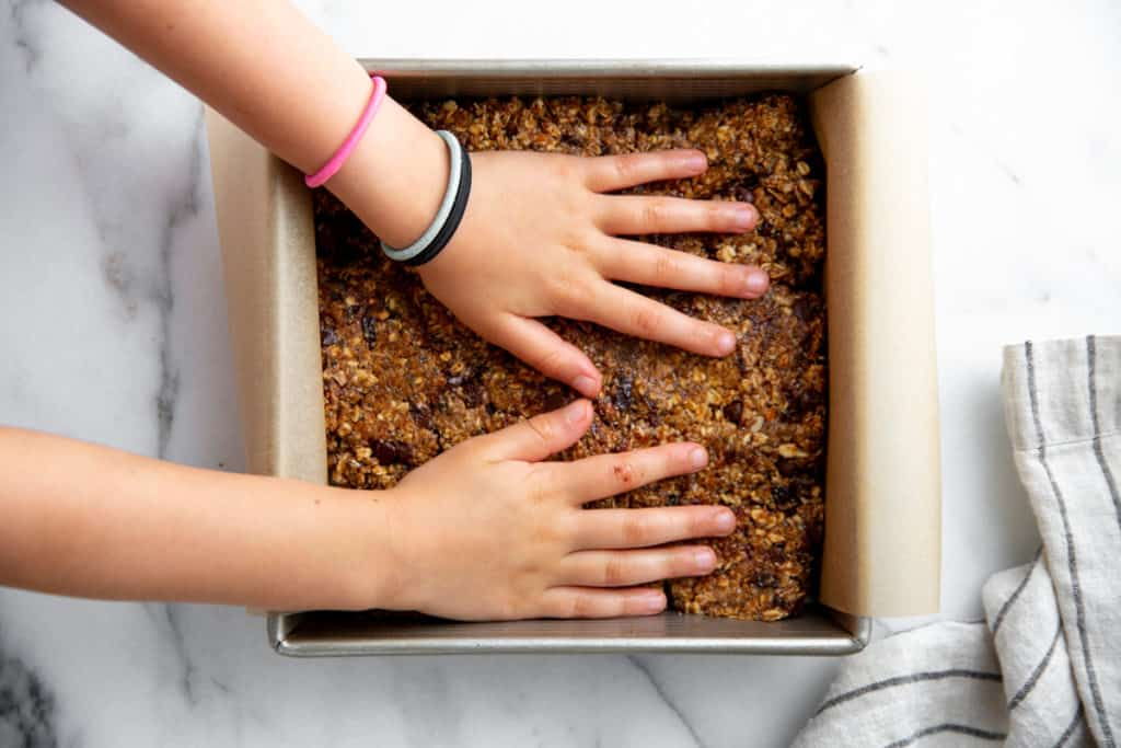 Two kids' hands pressing the no-bake cookie dough into an eight-by-eight inch pan.
