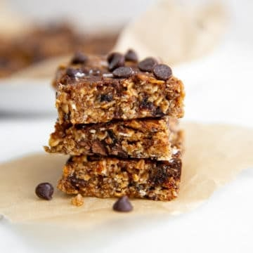 Vegan no bake chocolate chip cookie bars stacked on a piece of parchment paper.