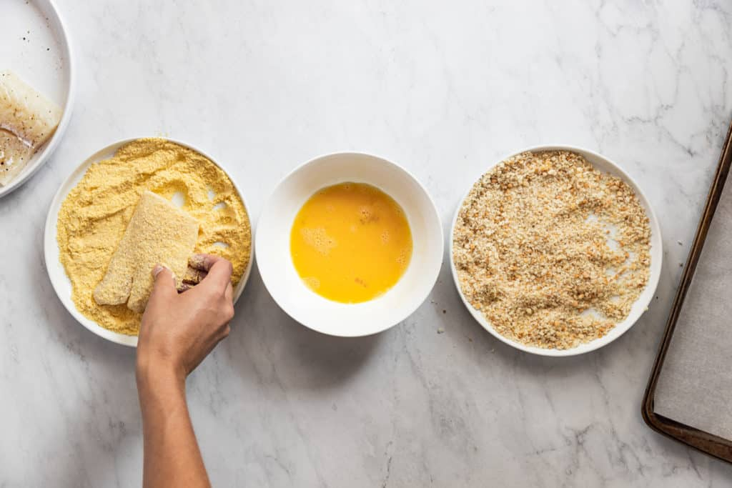 Process shot showing how to bread fish, showing a bowl of corn flour, a bowl of beaten eggs and a bowl of panko breadcrumbs.