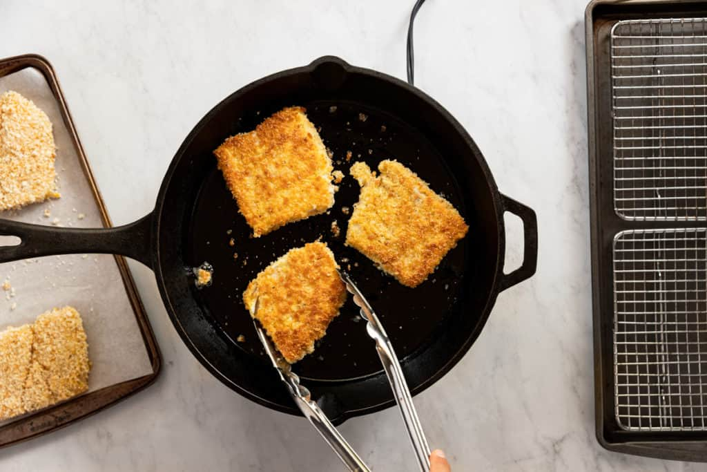 Breaded fillets of cod pan-frying in a cast iron skillet.