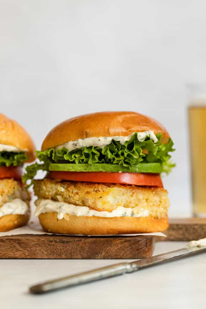 A fried fish sandwich with tomato and avocaod on a serving board.