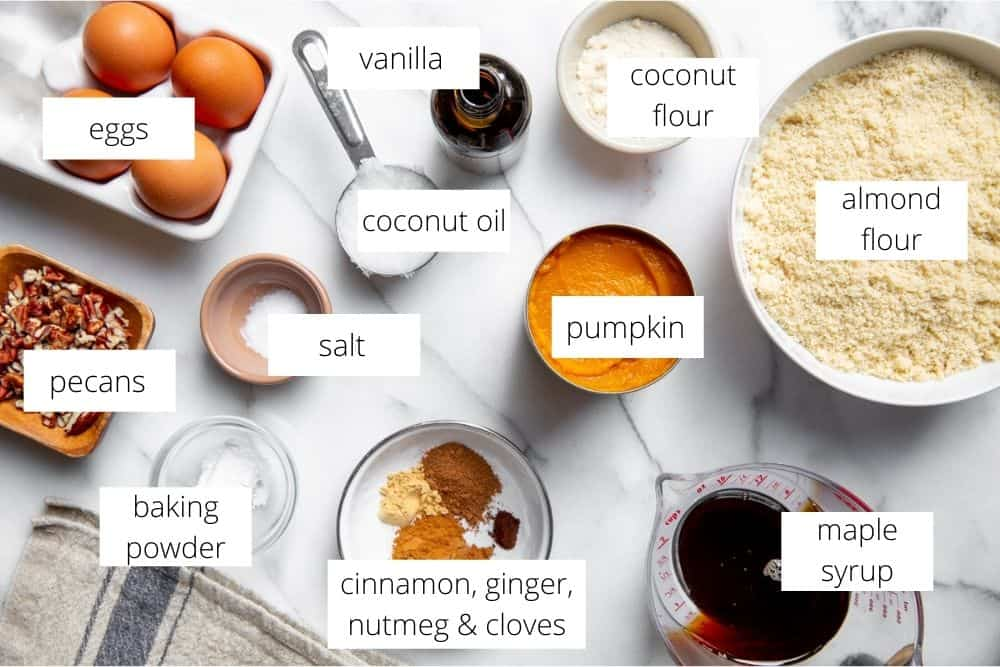 All of the ingredients for the gluten free pumpkin muffins recipe arranged on a marble surface with labels.