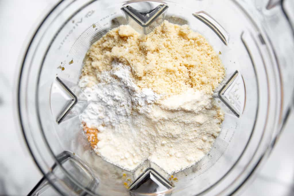 Process shot showing the dry ingredients on top of the wet ingredients in a blender.