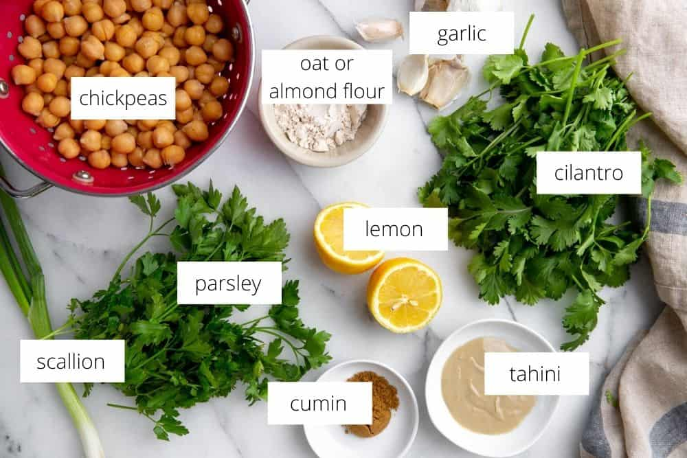 All of the ingredients for the healthy pan fried falafel recipe arranged on a marble surface with labels.
