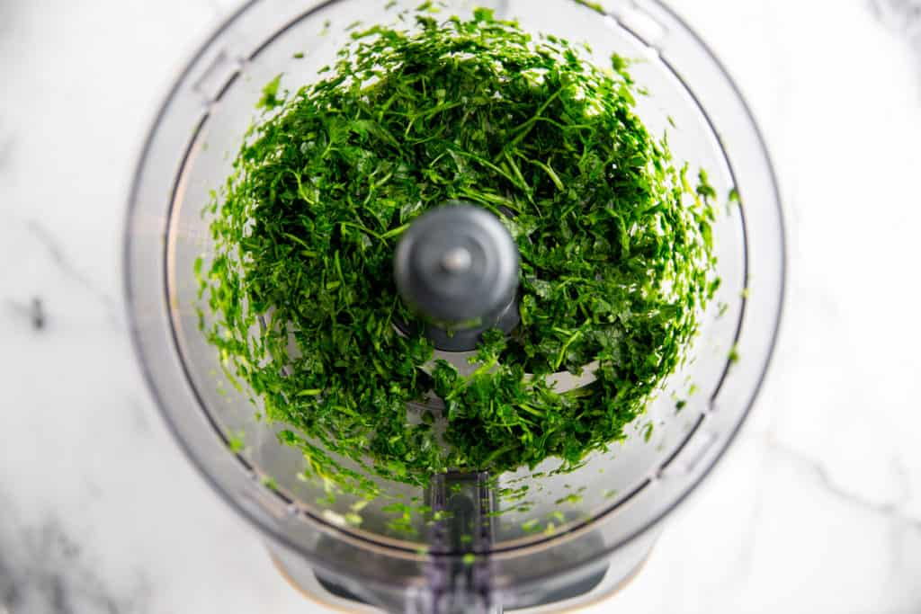 Process shot showing chopped herbs in a food processor.