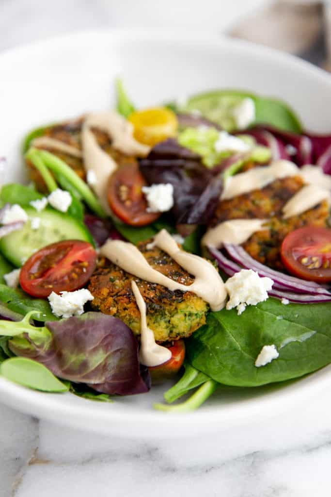Falafel over salad greens with red onion, tomatoes, cucumber, feta and creamy tahini sauce.
