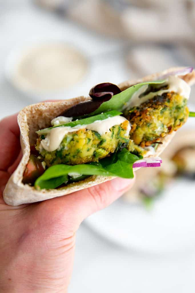 A hand holding a pita sandwich stuffed with pan fried falafel and tahini sauce.