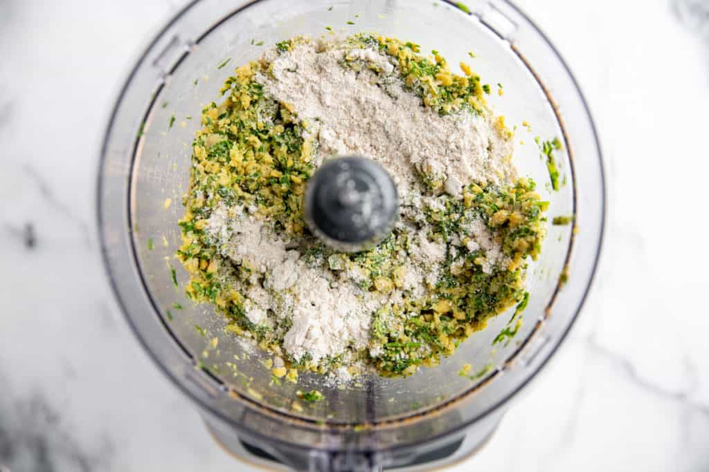 Oat flour sprinkled over the healthy falafel mixture in a food processor.