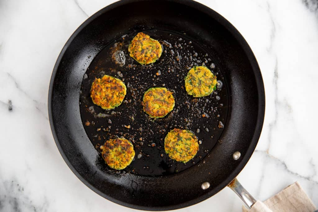 Falafel patties cooking in a non-stick skillet.