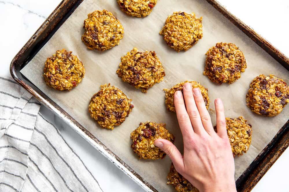 Process shot showing a hand flattening a pumpkin breakfast cookie.