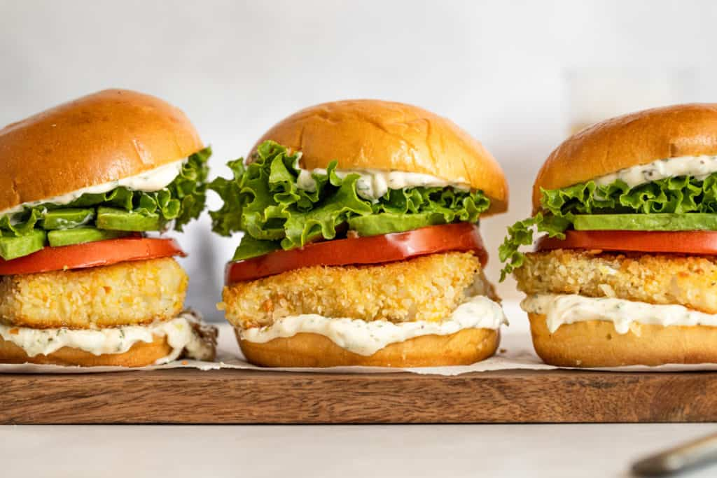 Tarragon aioli on fried fish sandwiches, which are lined on a serving board.