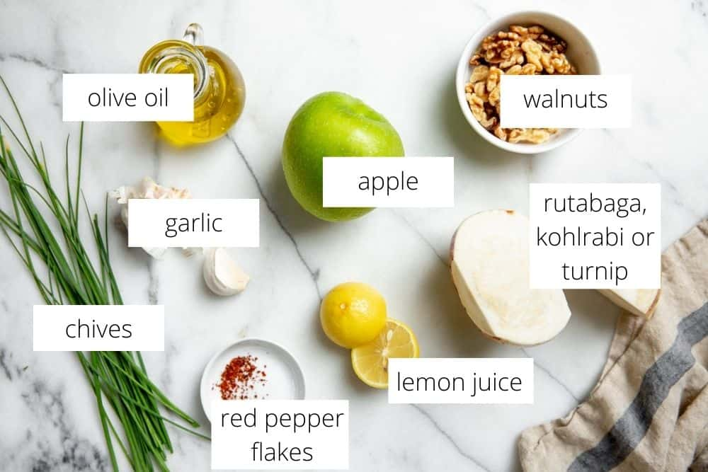 The ingredients for the apple slaw recipe on a marble surface with labels.