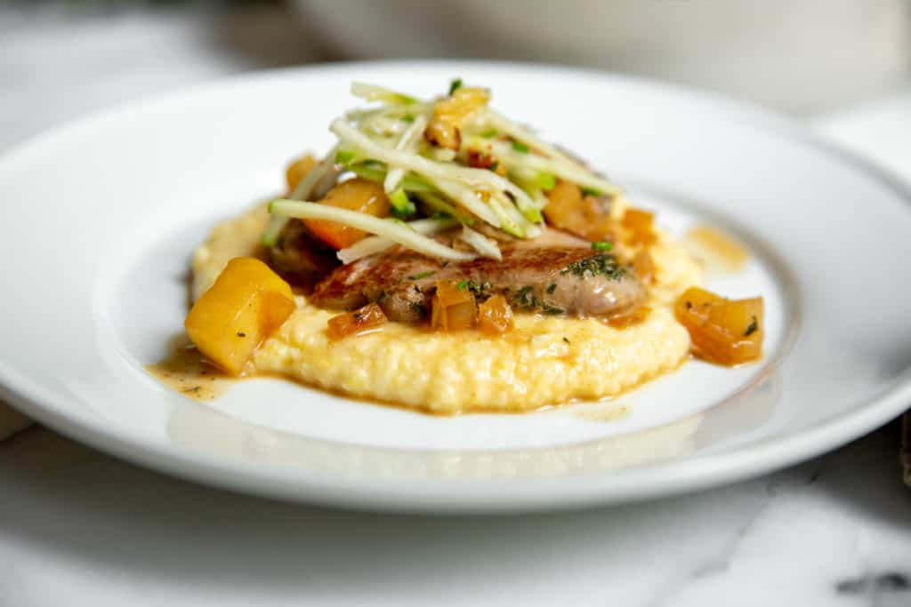 Pork medallions on a bed of polenta, topped with apple slaw.
