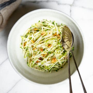 No mayo green apple slaw in a bowl with serving spoons.