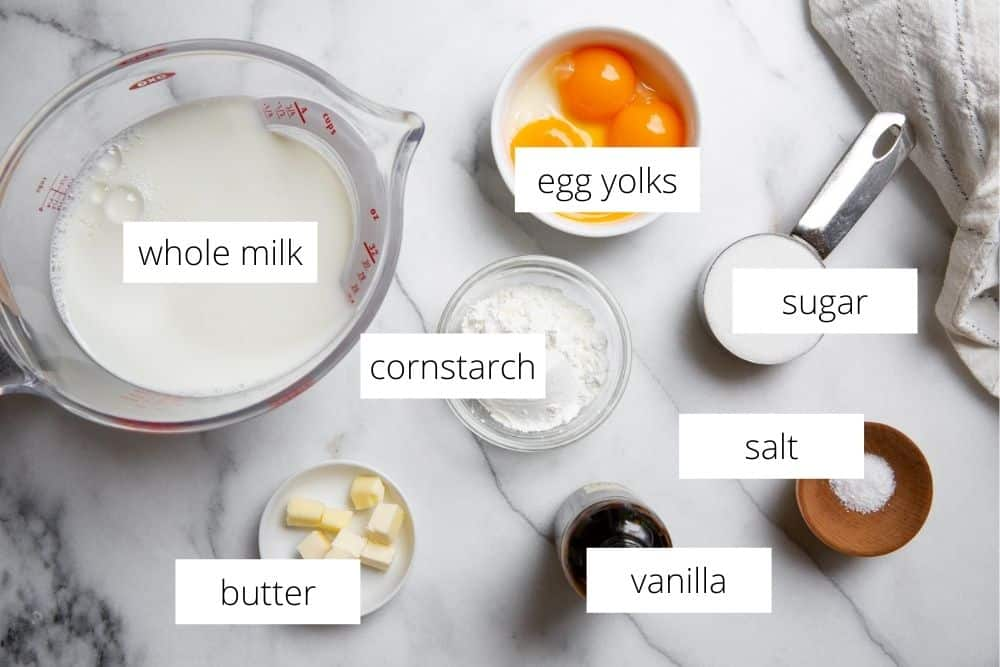 All of the ingredients for the homemade vanilla pudding recipe arranged on a marble surface with labels.