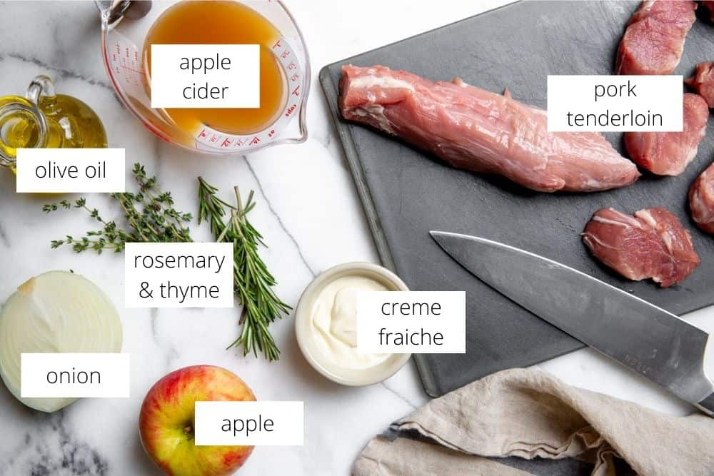 All of the ingredients for the pork tenderloin medallions with apples and onions recipe on a marble surface with labels.